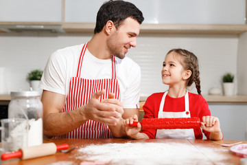 Children, baking, family concept. Cheerful brunet male wears apron and kneads dough, happy girl holds rolling pin, ready to help her father, sit together at kitchen, prepare dough for cookies.