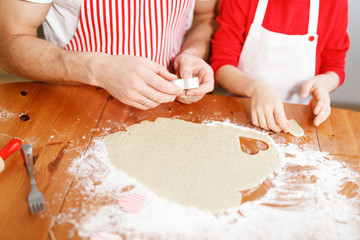 Cropped shot of unrecognizable hard working father and small daughter sit together at wooden table, make forms from dough, prepared puff pastry, surrounded with flour. Baking and cooking concept.