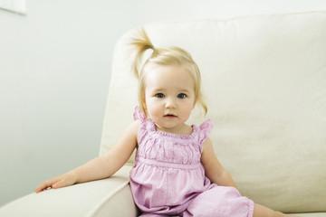Portrait of cute baby girl sitting on sofa