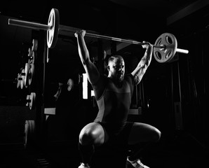 Professional powerlifter lifts the bar above his head in a squat