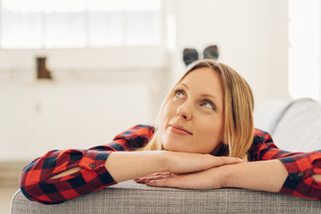 Young woman relaxing on a sofa daydreaming