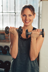 Cute slender young woman lifting weights
