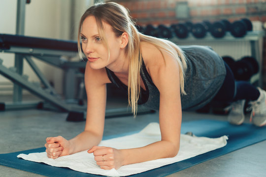Determined fit woman exercising forearm plank