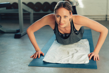 Young woman working out doing press-ups in a gym