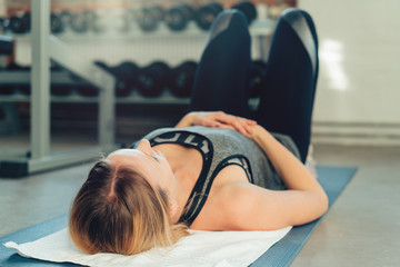 Young woman working out on a mat in a gym