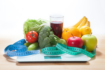 Healthy diet, fitness and weight loss concept, scales, measuring tape, fruits, vegetables on the table.