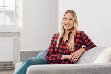 Smiling relaxed young woman sitting on a sofa