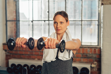 Determined woman exercising with dumbbells