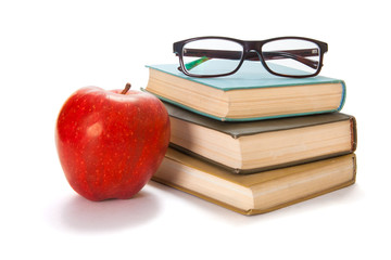 Three old books, glasses and a red apple on a white background