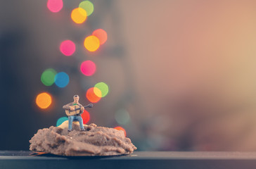 miniature man playing guitar on cookie with background of colourful bokeh light