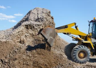 Wheel excavator digging  gravel pile for loading in  truck