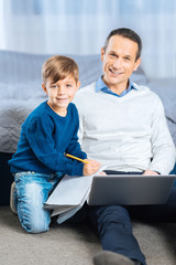 Creativity vibes. Adorable little boy sitting on the bedroom next to his father and copying the image from the laptop, drawing it in a drawing book, while both of them smiling at camera
