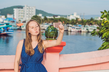 Beautiful young cheerful woman taking a selfie against the background of the sea and Vietnamese boats