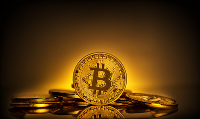 Bitcoin standing on the background of scattering of coins