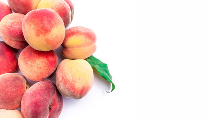 Heap of fresh ripe peaches with leaves on white background.