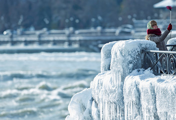 A visitor takes pictures of ice covered Niagara Falls in Niagara