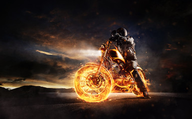 Dark motorbiker staying on burning motorcycle in sunset light Wall mural