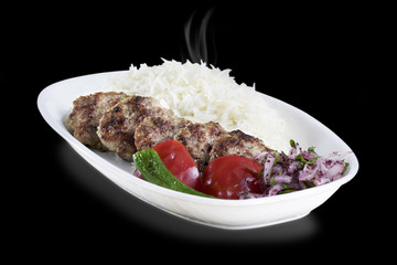 Grilled Meatbals served with rice tomato and spicy pepper on White Plate isolated on dark background
