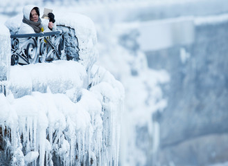 A visitor takes pictures near the brink of the ice covered Horseshoe Falls in Niagara Falls