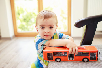 Little kid holding bus toy
