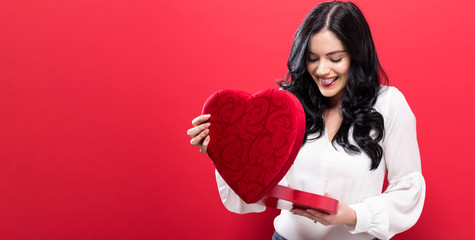Happy young woman holding a big heart gift box on a solid background