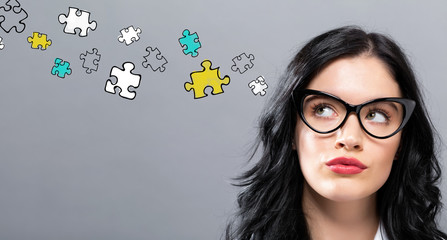 Puzzle Pieces with young businesswoman in a thoughtful face