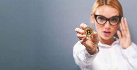 Woman holding a physical bitcoin cryptocurrency in her hand