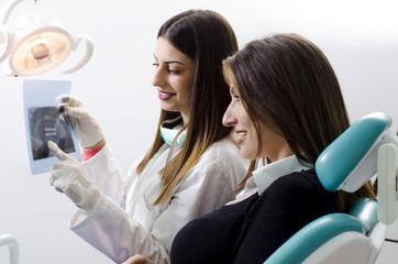 Female dentist showing x-ray of teeth to her patient and explaining