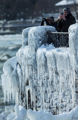 Visitors take pictures near the brink of the ice covered Horseshoe Falls in Niagara Falls,