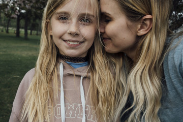 Close-up portrait of girl with mother at park