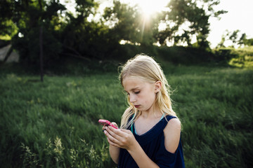 Girl using mobile phone while standing on grassy field