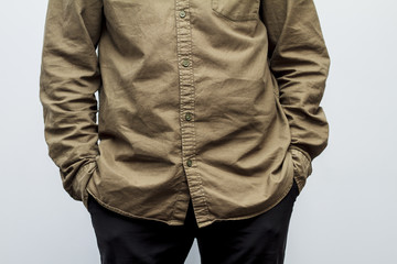 Part of a man's body dressed in brown shirt and keeping his hand in the pockets isolated on the white background. Selective focus and shallow DOF