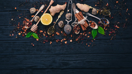 Assortment of dry teas and fragrant herbs and spices. On a wooden background. Top view. Copy space.