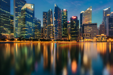 Singapore city skyline. Business district view. Downtown reflected in water at dusk in Marina Bay. Travel cityscape