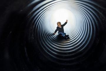 Full length of boy sliding in slide at park