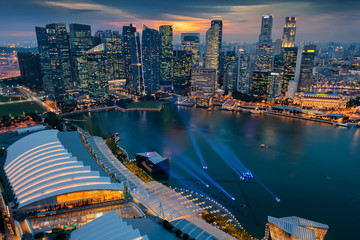 Singapore city skyline. Business district aerial view. Downtown landscape reflected in water at sunset in Marina Bay