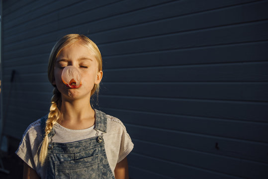 Girl with eyes closed blowing bubble gum while standing by wall