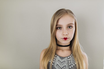 Portrait of girl with heart shape lipstick standing against wall