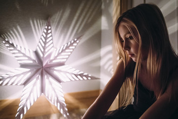Girl looking at illuminated star shape decoration