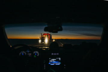 Truck on road seen through car windshield against sky during sunset