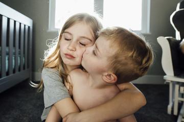 Shirtless boy kissing sister while sitting at home