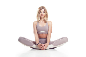 Studio portrait of a caucasian happy girl on a white background. Cute young blonde doing yoga. A girl with a smile in yoga clothes does the exercise.