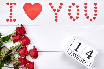 Valentines Day background with bouquet of red roses, sign I Love you made from paper hearts and february 14 wooden block calendar, copy space. Greeting card mockup. Love concept. Top view, flat lay