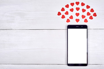 Close up of mobile smart phone with white blank screen and red paper hearts on wooden background, copy space. Flat lay, top view. Application mock up template