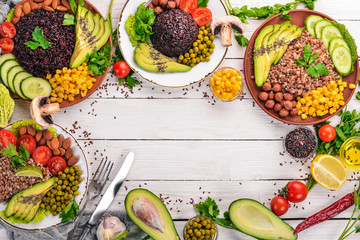 Healthy food. Black rice, buckwheat, avocado, cherry tomatoes, green peas and hazelnut. On a wooden background. Top view. Free space for your text.