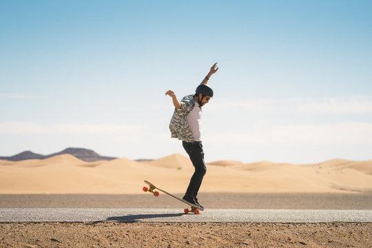 Man skateboarding on road against blue sky during sunny day