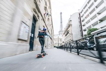 Full length rear view of woman skateboarding on footpath against Eiffel tower