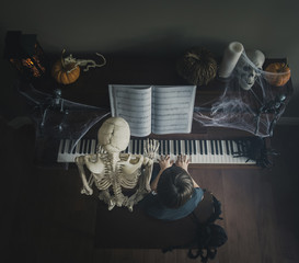 High angle view of boy playing piano while sitting by skeleton during Halloween