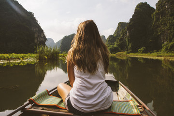 Rear view of woman looking at view while traveling in boat on river