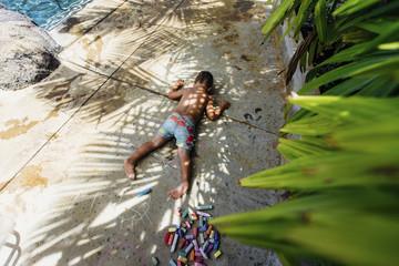 High angle view of shirtless boy lying on footpath